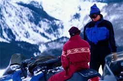 Des motoneigistes dans les montagnes